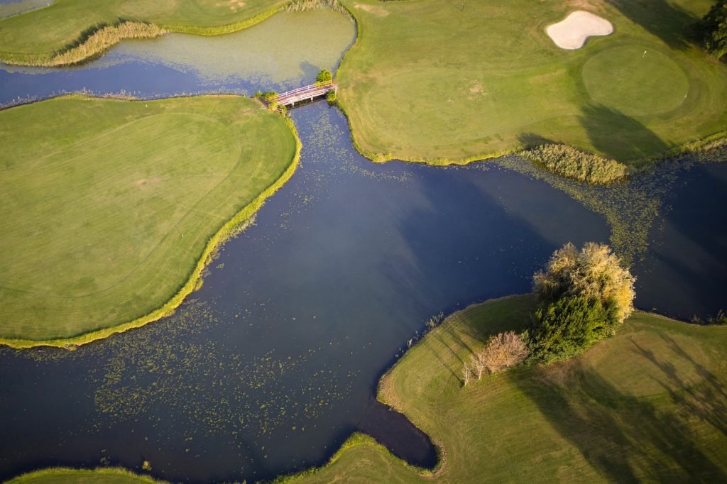 Golfbana med green, vatten och bunker