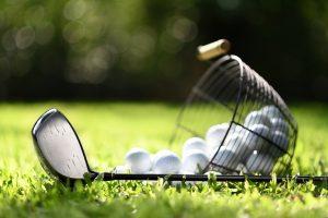 Golfklubb och korg med golfbollar