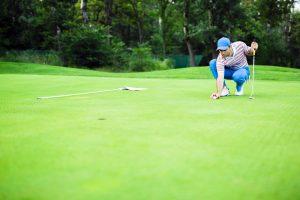 Golfspelare placerar boll inför putt