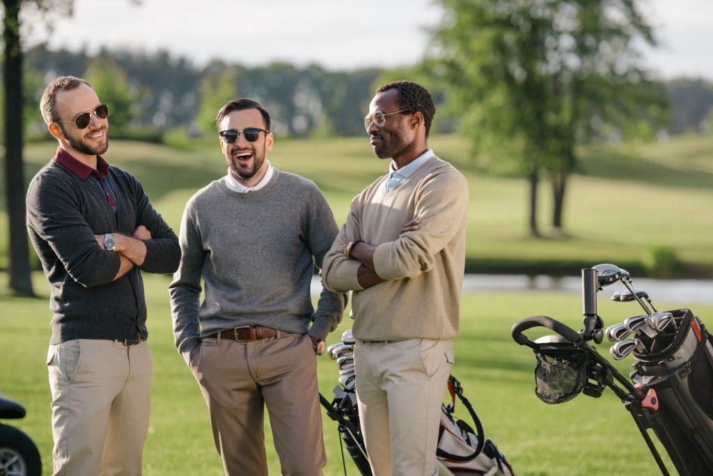 Glada golfspelare med golfväskor