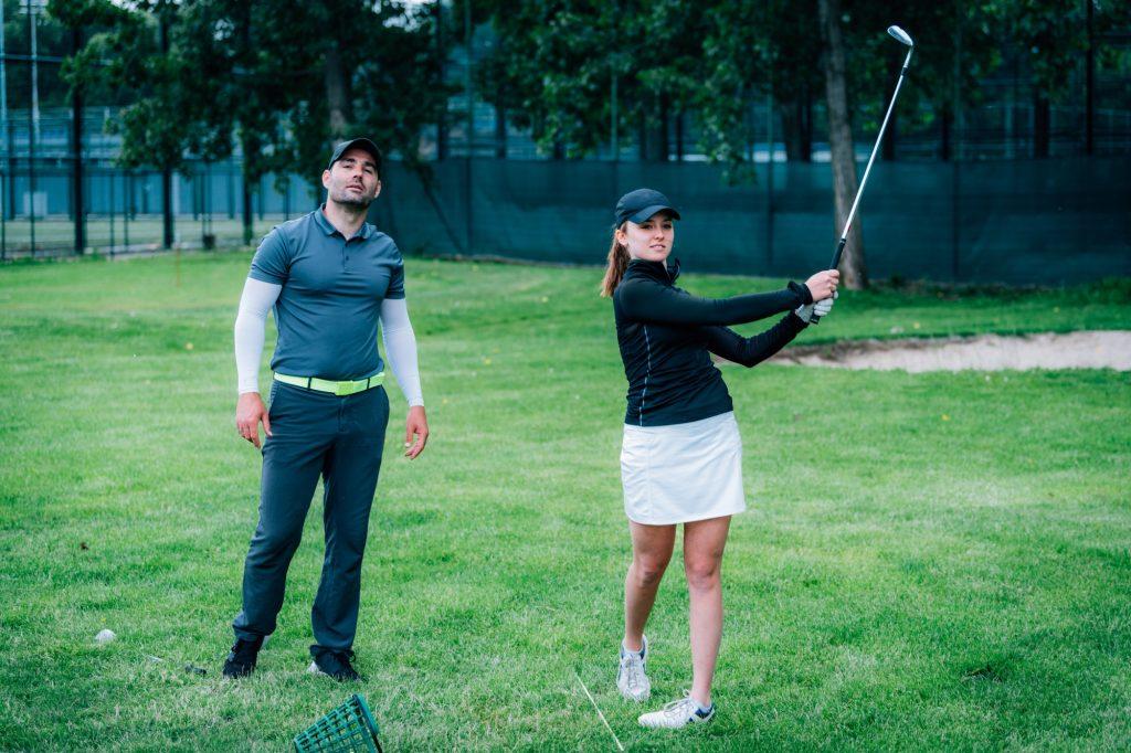 Golfinstruktör lär kvinnlig golfspelare att spela